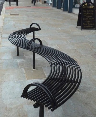 Black powder coated curved bench from benchmark street furniture